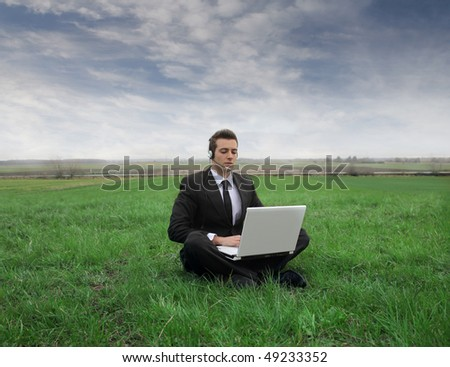 Businessman sitting on a green meadow with a laptop on his knees
