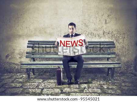 Businessman sitting on a park bench and reading a newspaper - stock photo