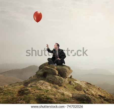 Businessman sitting on a rock and holding a balloon - stock photo