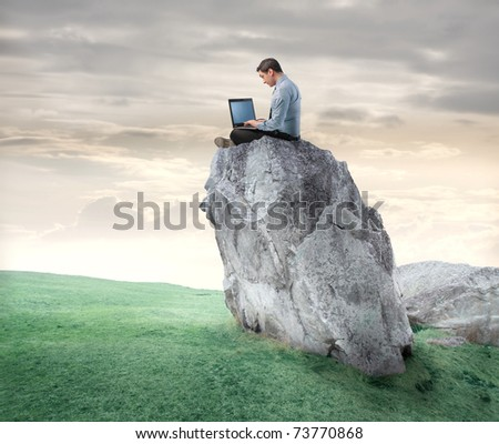 Businessman sitting on a rock and using a laptop - stock photo