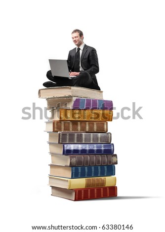 Businessman sitting on a stack of books and using a laptop - stock photo