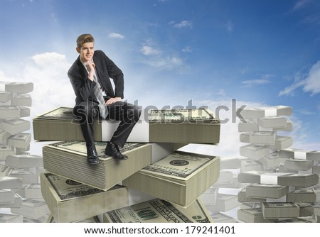 Businessman sitting on a stack of money  - stock photo