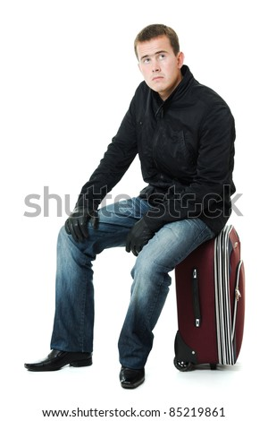 Businessman sitting on a suitcase.