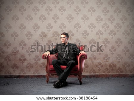 Businessman sitting on a velvet armchair - stock photo