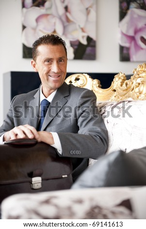 Businessman sitting on a vintage sofa, maybe waiting for someone - stock photo