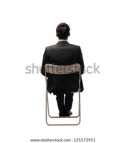 Businessman sitting on a white chair in a completely white location - stock photo