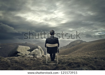 Businessman sitting on a white chair in front of a mountains wasteland - stock photo