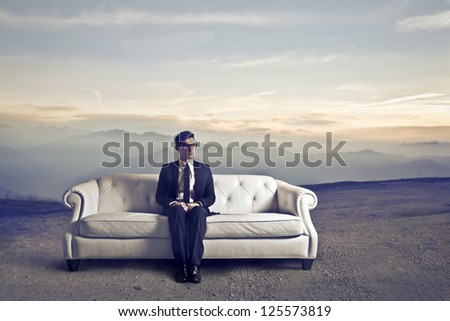Businessman sitting on a white sofa in a wasteland - stock photo