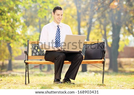 Businessman sitting on a wooden bench and working on a laptop in a park - stock photo