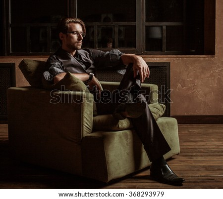 Businessman sitting on an armchair - stock photo