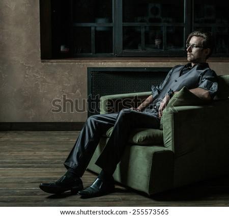 Businessman sitting on an armchair. Fahion man. - stock photo