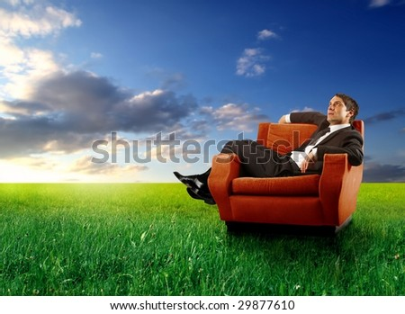 businessman sitting on an armchair in a grass field - stock photo
