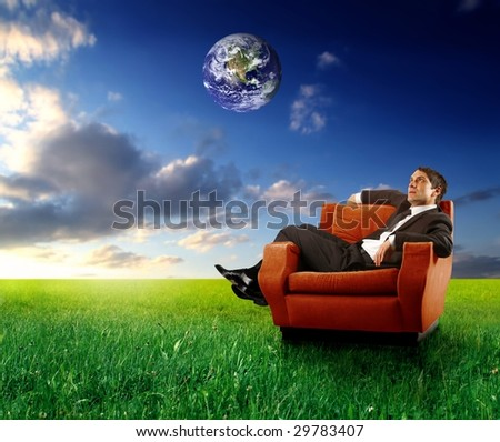 businessman sitting on an armchair in a grass field with planet earth in the sky - stock photo