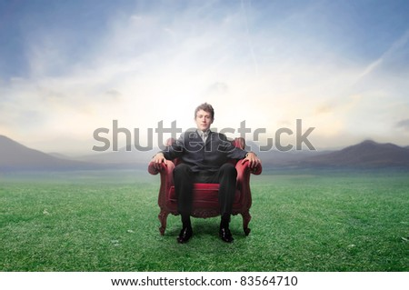 Businessman sitting on an armchair on a green meadow - stock photo