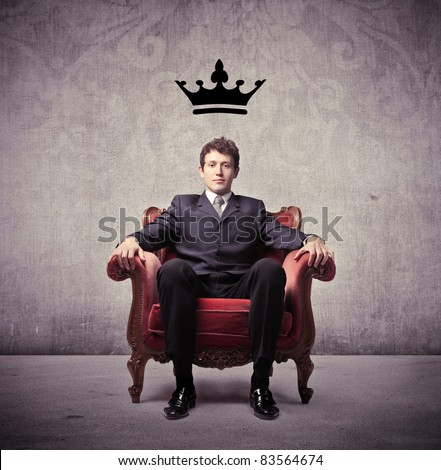 Businessman sitting on an armchair with a crown over his head - stock photo