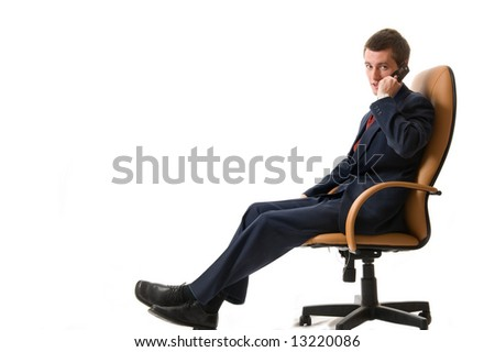 Businessman sitting on an armchair with cell phone. Isolated