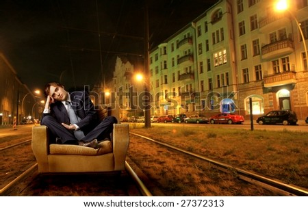 businessman sitting on armchair in a city street - stock photo