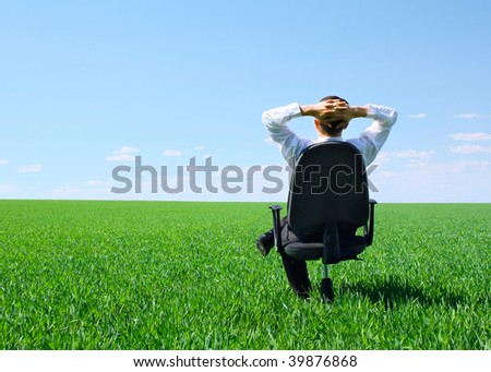 Businessman sitting on chair in green field - stock photo