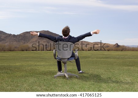 Businessman sitting on chair on green meadow on blue sky background - stock photo