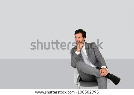 Businessman sitting on chair on grey background - stock photo