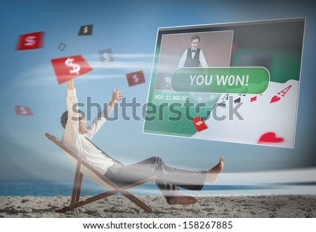 Businessman sitting on deck chair looking at holographic screen on the beach - stock photo