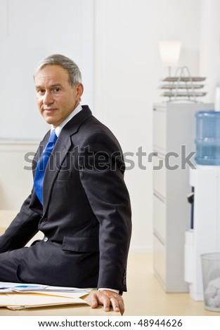 Businessman sitting on desk - stock photo
