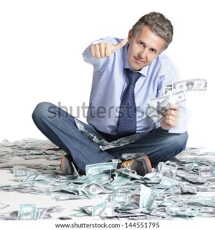 Businessman sitting on dollars banknotes - stock photo
