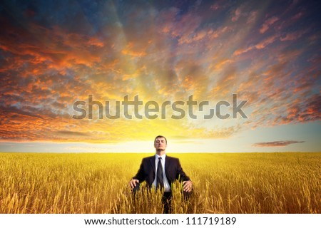 businessman sitting on filed in lotus pose, sunset time - stock photo