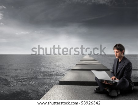 Businessman sitting on pads over the sea and using a laptop - stock photo