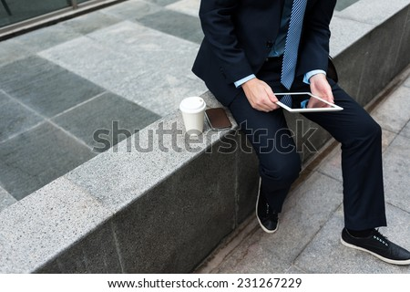 Businessman sitting on parapet and reading some information on the digital tablet - stock photo