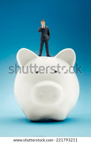 Businessman sitting on piggy bank - stock photo