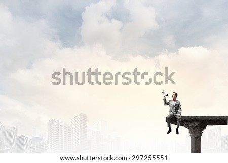 Businessman sitting on rock edge and screaming in megaphone - stock photo