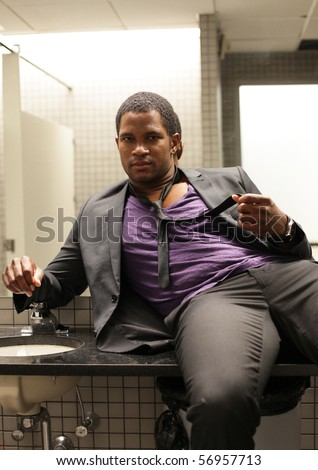 Businessman sitting on sink in Bathroom - stock photo