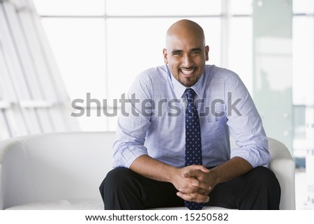 Businessman sitting on sofa in office lobby - stock photo