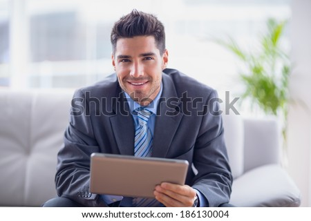 Businessman sitting on sofa using his tablet smiling at camera in the office
