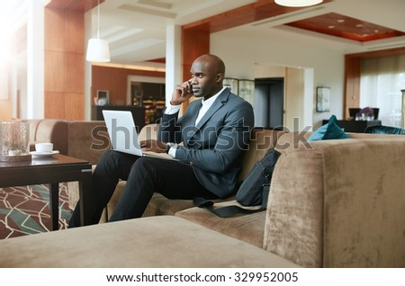 Businessman sitting on sofa with a laptop using mobile phone. Busy african male executive waiting in hotel lobby. - stock photo