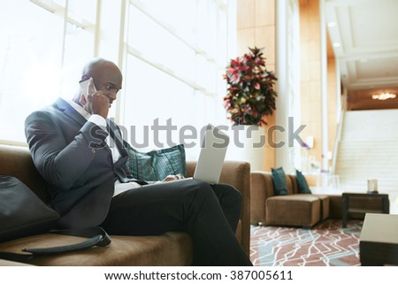 Businessman sitting on sofa working using cell phone and laptop. African male executive waiting in hotel lobby. - stock photo