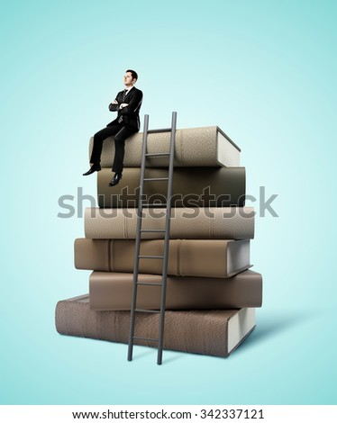 businessman sitting on stack of books with ladder - stock photo