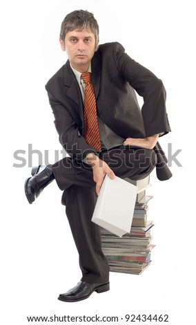 Businessman sitting on stacked books and holding empty white book as template - stock photo