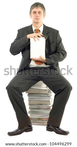Businessman Sitting on Stacked Books Presenting Empty White Hardcover Book - stock photo
