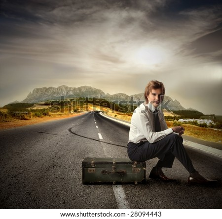 Businessman sitting on suitcase on a country road - stock photo