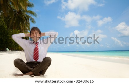 Businessman sitting on the beach and relaxing - stock photo