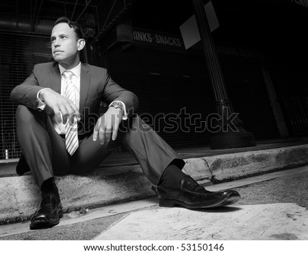 Businessman sitting on the curb.  Image in black and white