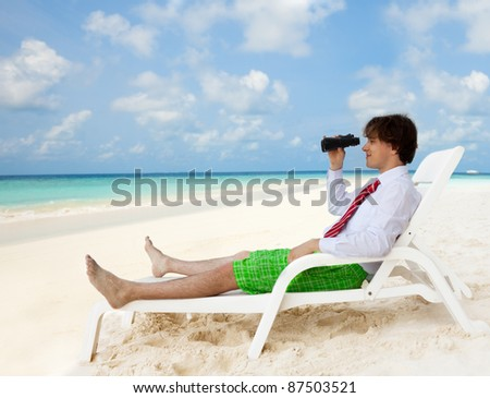 Businessman sitting on the deckchair and looking through binoculars, wearing formal shirt and red tie - stock photo