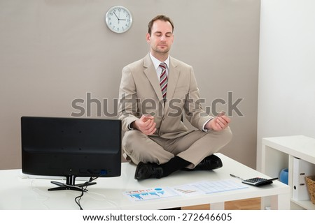 Businessman Sitting On The Desk And Meditating With Eyes Closed - stock photo