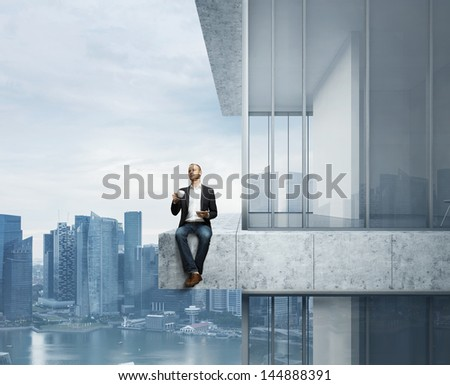Businessman sitting on the edge with cup of coffee