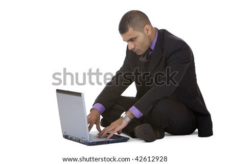 Businessman sitting on the floor and works on his laptop. Isolated on white background. - stock photo