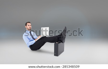 Businessman sitting on the floor with feet up on suitcase against grey vignette
