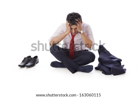 Businessman sitting on the floor with his head in hands