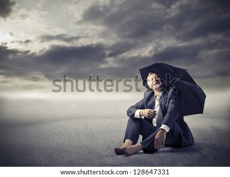 businessman sitting on the ground in the desert with umbrella - stock photo